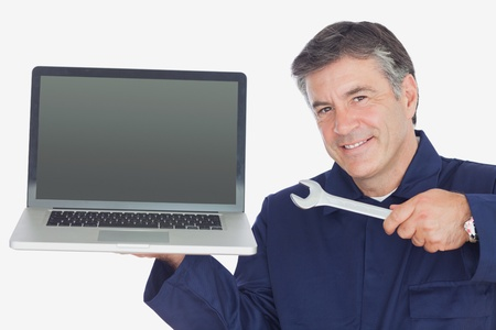 Portrait of mature mechanic holding wrench and laptop against white background photo