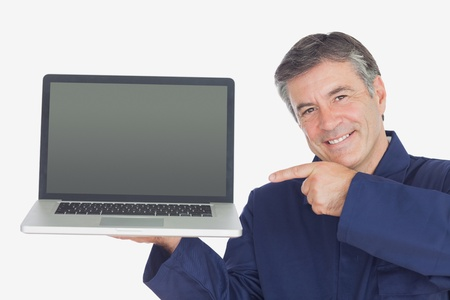 Portrait of happy mechanic pointing at laptop over white background photo