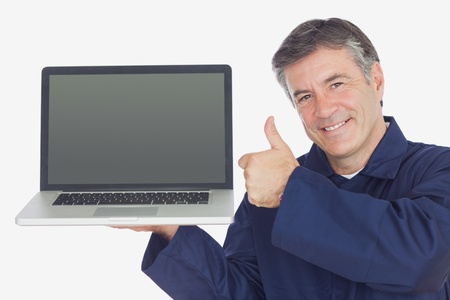 Portrait of happy mechanic with laptop showing thumbs up sign against white background photo