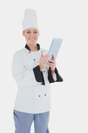 Portrait of happy female chef holding digital tablet over white background photo