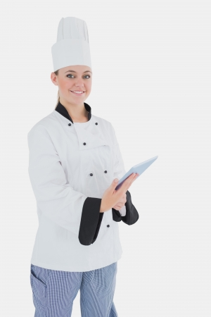 Portrait of happy female chef with digital tablet standing against white background photo