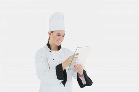 Happy female chef using glass tablet over white background photo