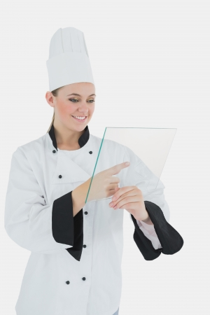 Happy young female chef with glass tablet over white background photo