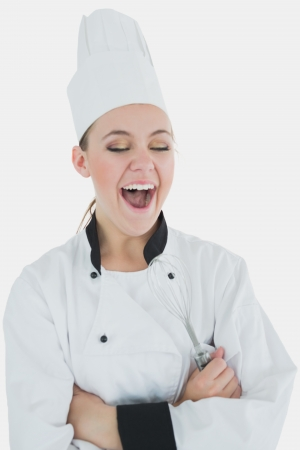 Female chef holding wire whisk as she laughs over white background photo