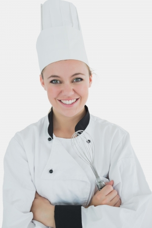 Portrait of happy female chef holding wire wisk over white background photo