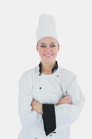 Portrait of confident female chef holding wire whisk against white background  photo