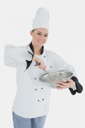wire whisk: Portrait of happy female chef holding wire whisk and mixing bowl against white background Stock Photo