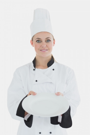 Portrait of female chef showing an empty plate over white background photo