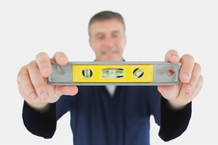 Mature male technician holding spirit level over white background Stock Photo