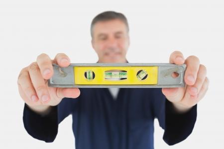 spirit level: Mature male technician holding spirit level over white background Stock Photo