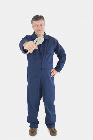 vise grip: Full length of mature mechanic with hand on waist holding vise grip against white background Stock Photo