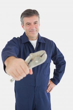 vise grip: Portrait of mechanic holding vise grip over white background