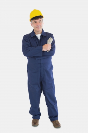 vise grip: Full length portrait of mature mechanic with hardhat holding vise grip over white background