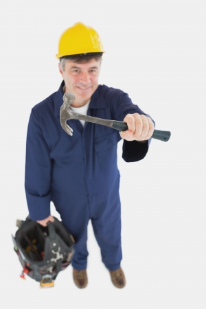 tool bag: Portrait of mechanic with hammer carrying tool bag against white background