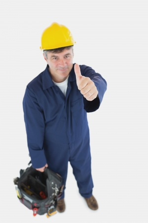 tool bag: High angle view of mature man with tool bag showing thumbs up sign over white background