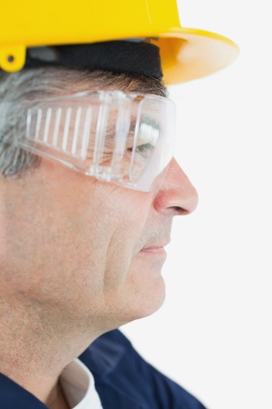 eye wear: Side view of technician wearing protective eye wear and hardhad looking away over white background Stock Photo