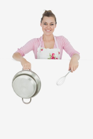 wire whisk: Portrait of young woman with wire whisk and mixing bowl standing behind billboard over white background