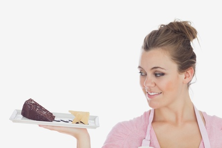 Close-up of young woman looking at pastry against white background photo
