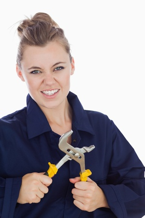 clenching teeth: Portrait of young female mechanic clenching teeth while holding pliers wrench over white background