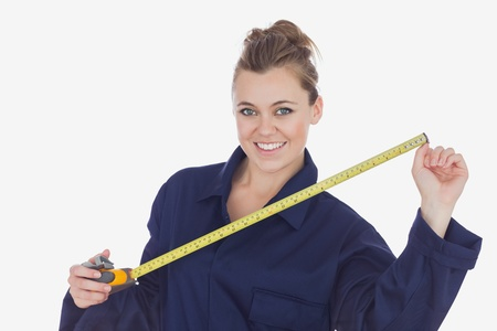 Portrait of happy female technician holding measuring tape over white background Stock Photo - 18101994