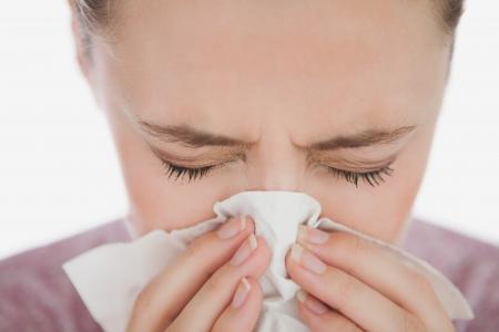 Vrouw met gesloten ogen blaast haar neus tegen de witte achtergrond