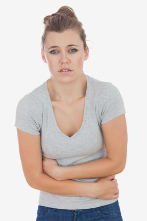 dolor de estomago: Retrato de una mujer joven que sufre de dolor de est�mago contra el fondo blanco Foto de archivo
