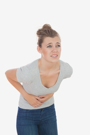 Young woman suffering from menstruation pain against white background