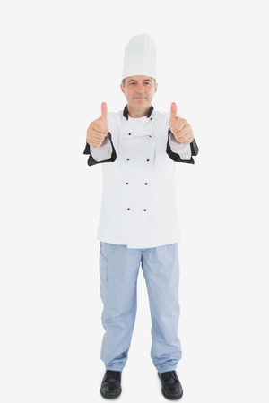 Full length portrait of mature male chef gesturing thumbs up over white background photo