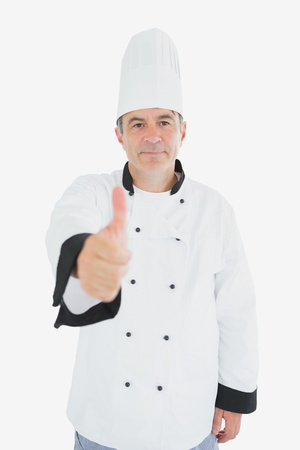 Portrait of mature chef showing thumbs up sign against white background photo