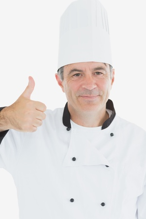 Portrait of chef in uniform showing thumbs up sign over white background photo