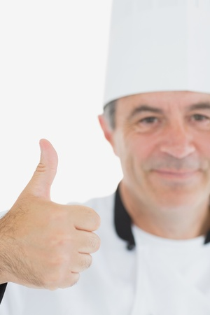Cropped image of mature chef showing thumbs up sign over white background photo