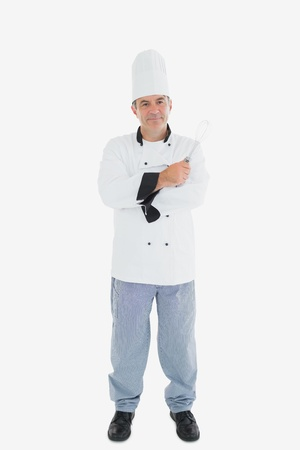 wire whisk: Full length portrait of male chef holding wire whisk over white background Stock Photo