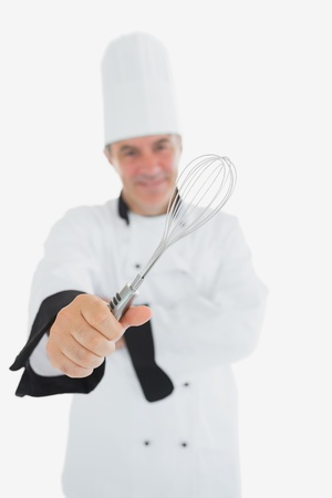 wire whisk: Portrait of male chef showing wire whisk over white background