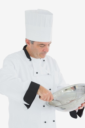 Mature male chef whisking ingredients in large bowl over white background photo