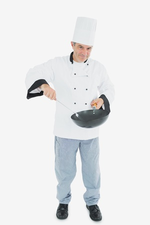 Full length portrait of confident male chef cooking food over white background photo
