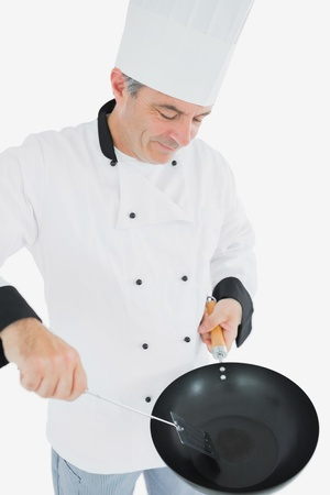 Male mature chef cooking food using spatula and frying pan over white background photo
