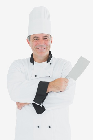 Portrait of happy chef holding meat cleaver over white background photo