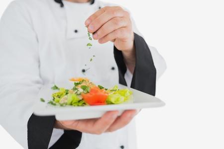 garnishing: Male chef garnishing fresh prepared meal over white background Stock Photo