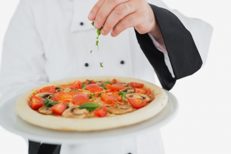 garnishing: Male chef garnishing pizza over white background