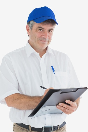 Portrait of confident courier man writing on clipboard against white backgorund photo