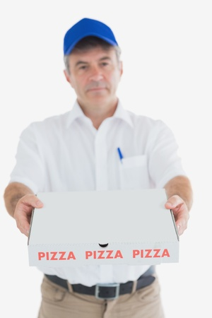 Portrait of mature pizza delivery man standing against white backgorund photo