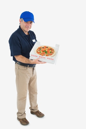 Portrait of mature pizza delivery man standing against white background photo
