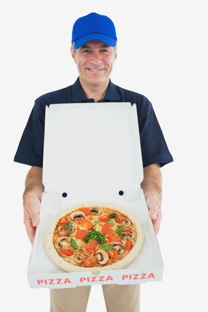 Portrait of happy pizza delivery man standing against white background photo