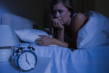 out of context: Unquiet blond woman in the bed at night in the bedroom Stock Photo