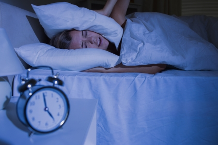Blond woman putting pillows on her ears at night Stock Photo