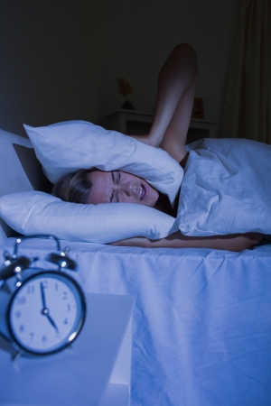offended: Offended woman putting pillows on her ears at night Stock Photo