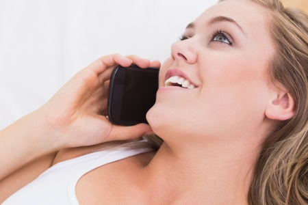 Blonde woman phoning in the white bedroom photo