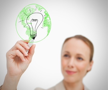 Smiling woman drawing picture of green globe and black bulb photo