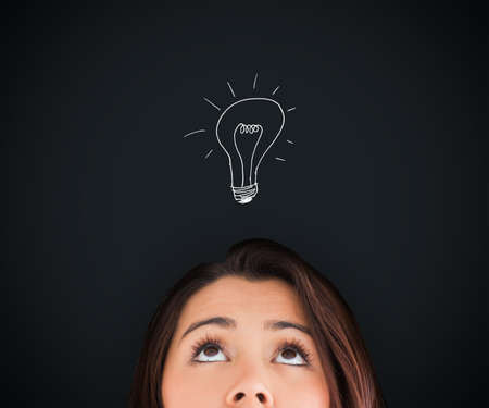 woman looking up: Woman looking up on the picture of white bulb above her head