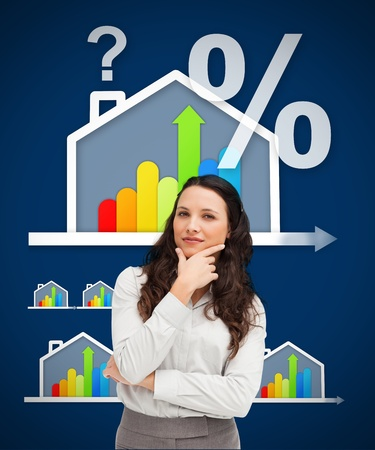 Thinking businesswoman standing against a energy efficient house graphic on blue background photo
